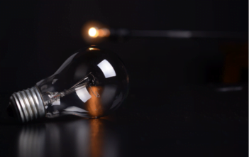 A unlit light bulb fading in a power outage.