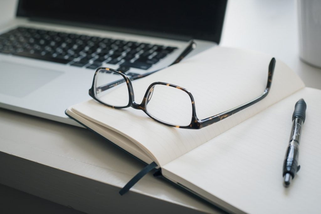 A notebook and glasses on a desk. An example of a set up a wrongful death lawyer might have.
