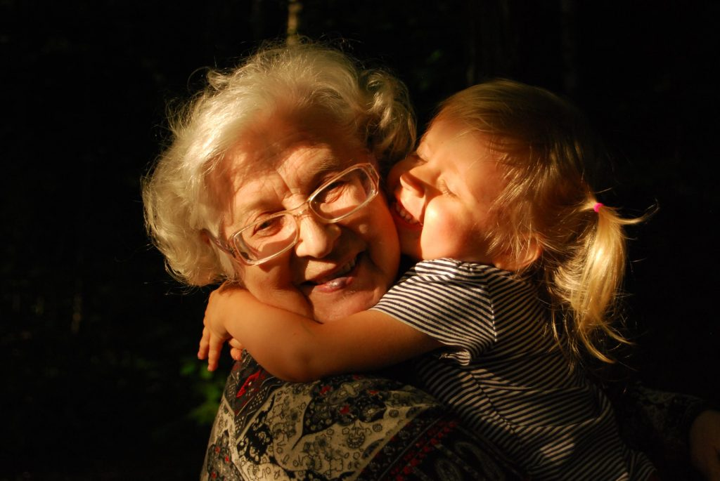 a senior grandma embrassing a child.